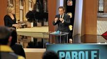 """Nicolas Sarkozy (R), France's President and UMP political party candidate in the 2012 French election, appears on the TF1 television programme """"Parole de candidat"""" (Word of the Candidate) on March 12, 2012. (PHILIPPE WOJAZER/Reuters/PHILIPPE WOJAZER/Reuters)"""