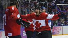 Canada forward John Tavares, right, and forward Jeff Carter, second from left, celebrate with defenseman Drew Doughty (8) after Doughty scored a sudden death overtime goal against Finland during a men's ice hockey game at the 2014 Winter Olympics, Sunday, Feb. 16, 2014, in Sochi, Russia. (Mark Humphrey/AP)