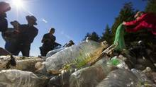A group of Japanese delegates sort through water bottles some of which are Japanese on beach on Wouwer Island near Ucluelet, BC September 26, 2013 to investigate the tsunami debris issue on B.C.'s west coast. (John Lehmann/The Globe and Mail)