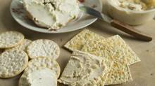 Cream cheese style with herb blend (cracker on left), cream cheese style with hot chili peppers (on cracker on right) cream cheese style with herb blend on bagel in foreground and cream cheese style on bagel in background. (Kevin Van Paassen/The Globe and Mail)