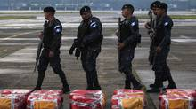 Police officers walk near packages containing cocaine seized from an anti-drug operation in the Izabal region, located about 264 kilometres from Guatemala City, at an air base in Guatemala City, October 23, 2013. (JORGE DAN LOPEZ/REUTERS)
