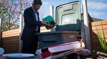 Vancouver Mayor Gregor Robertson demonstrates the use of a new household green bin used to recycle food scraps in Vancouver, B.C., on Thursday April 11, 2013. The small bins are to be used in homes and then emptied into larger bins that will be collected by the city weekly. (Darryl Dyck for The Globe and Mail)