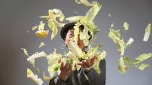 Sang Kim, Toronto chef and owner of several restaurants, tosses napa cabbage into the air. (Peter Power for The Globe and Mail)