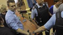 Russian protest leader Alexei Navalny, left, is handcuffed and escorted by interior ministry officers inside a courtroom in Kirov on July 18, 2013. A Russian judge sentenced protest leader Alexei Navalny to five years in prison on Thursday after convicting him of large-scale theft in a trial Mr. Navalny said was politically motivated. (REUTERS)