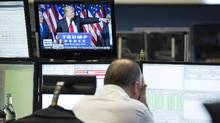 A trader reacts as a television news report shows U.S. President-elect Donald Trump speaking following the U.S. Presidential election result announcement, inside the Frankfurt Stock Exchange in Frankfurt, Germany, on Wednesday, Nov. 9. (Alex Kraus/Bloomberg)