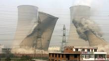 In this Oct. 28, 2009 file photo, two cooling towers are demolished at a coal burning power plant as an effort to improve energy efficiency in Xinxiang, in central China's Henan province