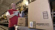 Glenn Pearce pulls and scans merchandise in the Amazon.com sorting area as he readies boxes for shipping in a file photo from March 17, 2004, at the massive Amazon.com shipping and receiving facility in Fernley, Nev. (SCOTT SADY/AP)