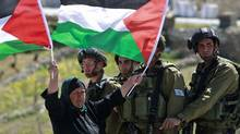A Palestinian woman holds up flags beside Israeli soldiers during a demonstration against the controversial barrier in the West Bank village of Ma'asarah, near Bethlehem, on March 27, 2009. (Ammar Awad/REUTERS)