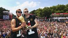 Germany's Mario Goetze (L) and Andre Schuerrle pose with the World Cup trophy during celebrations to mark the team's 2014 Brazil World Cup victory, at a 'fan mile' public viewing zone in Berlin July 15, 2014. (ALEX GRIMM/REUTERS)
