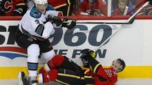 Calgary Flames' Matt Stajan (R) gets knocked to the ice by San Jose Sharks' Douglas Murray during the first period of their NHL game in Calgary, Alberta, January 20, 2013. (TODD KOROL/REUTERS)