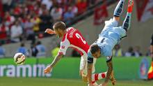 Arsenal's Mathieu Debuchy is challenged by Manchester City's Aleksandar Kolarov during their English Community Shield soccer match at Wembley Stadium in London, August 10, 2014. (Suzanne Plunkett/Reuters)