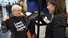 A delegate checks out a souvenir t-shirt on the first day of the federal New Democratic Party's weekend national policy convention Friday, April 12, 2013 in Montreal. (Ryan Remiorz/THE CANADIAN PRESS)