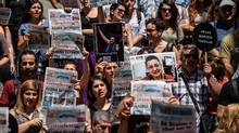 Protesters, in a demonstration last June in Istanbul, hold pictures of Turkish journalists and rights activists who were arrested for alleged 'terrorist propaganda.' (OZAN KOSE/AFP/Getty Images)