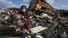 Aiko Musashi carries personal belongings from her destroyed home on March 18, 2011 in Kesennuma, Japan. (Paula Bronstein/Paula Bronstein/Getty Images)