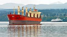 The STX Daisy, left, floats at anchor in Port Angeles Harbor as the MV Coho, right, pulls into its dock. (Chris Tucker/Peninsula Daily News/Chris Tucker/Peninsula Daily News)