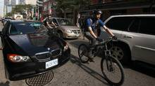 A woman sits in her illegally parked car during rush hour on King Street West as cyclists make comments about her also being on the phone as they and other vehicles manoeuvre around her stopped car in Toronto, Ontario, Canada. (The Globe and Mail/Deborah Baic/The Globe and Mail/Deborah Baic)