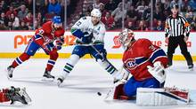 Carey Price makes a stick save while teammate Alexander Radulov defends against Daniel Sedin during Wednesday's game. (Minas Panagiotakis/Getty Images)