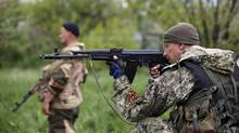 A pro-Russian rebel aims his rifle at a checkpoint near a Ukrainian airbase in Kramatorsk, eastern Ukraine, on May 2, 2014. (MARKO DJURICA/REUTERS)