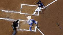 Milwaukee Brewers' Jonathan Lucroy slides safely past Toronto Blue Jays catcher Dioner Navarro, center, during the first inning of a baseball game Tuesday, Aug. 19, 2014, in Milwaukee. (Morry Gash/AP)