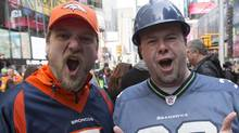 "Denver Broncos fan Nathan Wilkes, left, and Seattle Seahawks fan Jim Rudd, both of Seattle, pose for photos on ""Super Bowl Boulevard"" at Times Square, as part of the Super Bowl lead up, in New York Feb. 1, 2014. (Andrew Kelly/Reuters)"