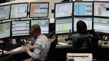 Traders are pictured at their desks at the Frankfurt stock exchange December 8, 2011. (PAWEL KOPCZYNSKI/REUTERS)
