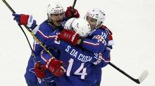 Stephane Da Costa of France (C) celebrates with team mates Antoine Roussel (L) and Yohann Auvitu (R) his second goal against Canada during the third period of their men's ice hockey World Championship Group A game at Chizhovka Arena in Minsk May 9, 2014. (VASILY FEDOSENKO/Reuters)
