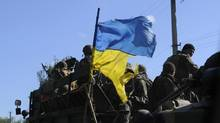 Ukrainian soldiers drive a military vehicle with a torn Ukrainian flag at a checkpoint near Slavyansk on July 3, 2014. (ANDREW KRAVCHENKO/REUTERS)