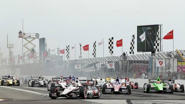 Will Power, of Australia, (12) leads the field at the start of the IndyCar series Honda Grand Prix of St. Petersburg auto race Sunday, March 24, 2013, in St. Petersburg, Fla. (Chris O'Meara/AP)