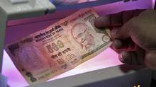 Indian currency is checked at a bank in Allahabad. Foreign lawyers will now be allowed to practise -- and make fees -- in India on a fly-in, fly-out basis. (Jitendra Prakash/Reuters/Jitendra Prakash/Reuters)