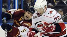 Carolina Hurricanes right wing Erik Cole (26) and Atlanta Thrashers defenseman Mark Stuart (5) battle for the puck during the second period of an NHL hockey game, Friday, April 8, 2011, in Atlanta. (AP Photo/John Amis) (John Amis)