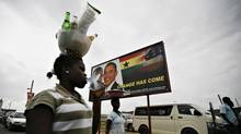 A woman carries goods on her head past a billboard depicting the likenesses of Ghana's President John Atta Mills and U.S. President Barack Obama in the Ghanaian town of Cape Coast July 9, 2009. (FINBARR O'REILLY/Reuters)