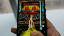 A woman uses an app called 'Clap for Xi Jinping' in Shanghai on October 19, 2017. (CHANDAN KHANNA/AFP/Getty Images)