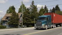 A transport trucks rumbles past an Arts and Craft house on River Road in Delta, BC, May 15, 2009. The South Fraser Perimeter Highway, a four-lane, 40-kilometre stretch of blacktop that is part of B.C.'s vaunted Gateway project and would link DeltaPort to highways in the Fraser Valley and run through South Delta along the Fraser River. The $1-billion project, for which prep work is beginning, skirts the Burns Bog conservation area and involves expropriation of dozens of homes (some estimates say 200). (Lyle Stafford for the Globe and Mail)