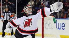 New Jersey Devils goalie Martin Brodeur (30) makes a save against the New York Islanders during the second period of a game at Nassau Veterans Memorial Coliseum. (USA TODAY Sports)