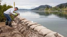 Malcolm Uttley places sandbags along a small canal between Kalamalka Lake and Wood Lake at the Tween Lake Resort in Oyama B.C., just north of the City of Kelowna, on May 12, 2017. Homeowners are being asked to build nearly one-metre high sandbag barriers to protect their property from possible flooding caused by rising water levels in British Columbia's Okanagan Lake. (Jeff Bassett/THE CANADIAN PRESS)