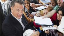 "Actor Tom Hanks greets fans as he arrives on the red carpet for the gala presentation of the film ""Cloud Atlas"" at the 37th Toronto International Film Festival, September 8, 2012. (MARK BLINCH/REUTERS)"