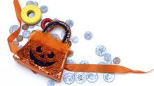 Halloween candy is expensive and adds up if you count in costumes, parties and transportation. Halloween purse and wooden candy lay across scattered coins. (nameinfame/Getty Images/iStockphoto)