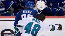 San Jose Sharks' Tomas Hertl loses his helmet as he collides with Vancouver Canucks' Alexander Edler during the second period of an NHL hockey game in Vancouver, B.C., on Thursday October 10, 2013. (The Canadian Press)