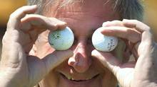 Alberta Premier Ralph Klein jokingly shields his eyes with a pair of golf balls during a break between playing holes at his charity golf tournament in Spruce Grove, Alta., on June 4, 2003. (DARRYL DYCK/CP / Edmonton Sun)