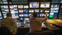 Senior producer Sherali Najak, left, and director Paul Hemming work in the broadcast truck during the airing of the CBC's Hockey Night in Canada, produced by Rogers Media, in a Dec. 6, 2014 file photo. (Mark Blinch For The Globe and Mail)