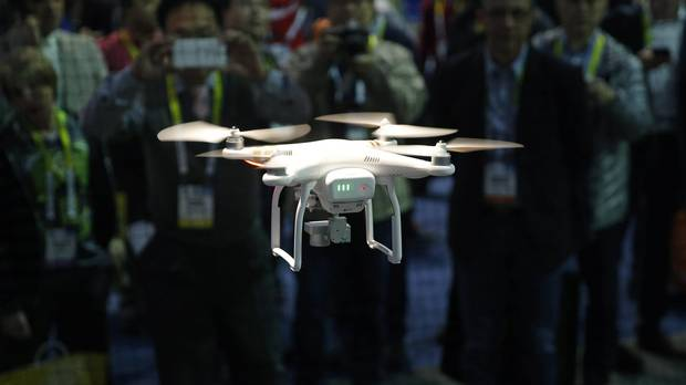 Companies across Canada are turning to drones to monitor crops, snap pictures for real estate listings and map the oil sands – and insurers are swooping in to cover the risk of hard landings and injuries. (John Locher/AP)