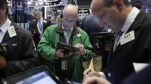 Trader Kevin Walsh, center, and specialist Andrew Silverman, right, work on the floor of the New York Stock Exchange, Wednesday, May 3. (Richard Drew/AP)