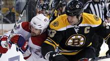 Boston Bruins defenseman Zdeno Chara (33) checks Montreal Canadiens right wing Brian Gionta (21) against the boards as they chase the puck during the first period of an NHL hockey game in Boston, Wednesday, Feb. 9, 2011. (AP Photo/Elise Amendola) (Elise Amendola)