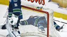 Vancouver Canucks defenceman Dan Hamhuis lies behind the net after he was knocked hard into the boards by Ryan Getzlaf of the Anaheim Ducks during Wednesday's game in Vancouver. (ANDY CLARK/Andy Clark/Reuters)