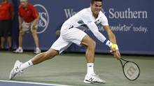 Milos Raonic, from Canada, returns a volley to Roger Federer, of Switzerland, during a semifinal at the Western & Southern Open tennis tournament, Saturday, Aug. 16, 2014, in Mason, Ohio. (David Kohl/AP)