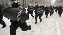 Riot police chase demonstrators during a protest against Quebec's plan for developing the province's north, Friday, February 8, 2013 in Montreal. (Ryan Remiorz/THE CANADIAN PRESS)