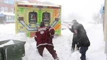 Two bystanders help a Montreal ambulance driver get his stuck vehicle out of a snow bank in Montreal on Dec. 27, 2012. (Francois Havill/THE CANADIAN PRESS)