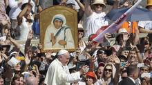 Pope Francis passes in front a portrait of Mother Teresa as he is driven through the crowd at the end of a canonization ceremony in St. Peter's Square at the Vatican, Sunday, Sept. 4, 2016. Francis declared Mother Teresa a saint on Sunday, praising the tiny nun for having taken in society's most unwanted and for having shamed world leaders for the 'crimes of poverty they themselves created.' (Alessandra Tarantino/AP)