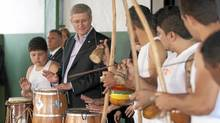 Prime Minister Stephen Harper plays the drums as he watches a capoeira performance at the Casa Sao Jose Community centre in Sao Paulo, Brazil Tuesday August 9, 2011. (Adrian Wyld/The Canadian Press/Adrian Wyld/The Canadian Press)
