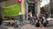Activists stand at the main entrance of a recently occupied Bankia branch in Madrid, with a banner reading 'Bankia is ours.' (Alberto Di Lolli/The Associated Press)